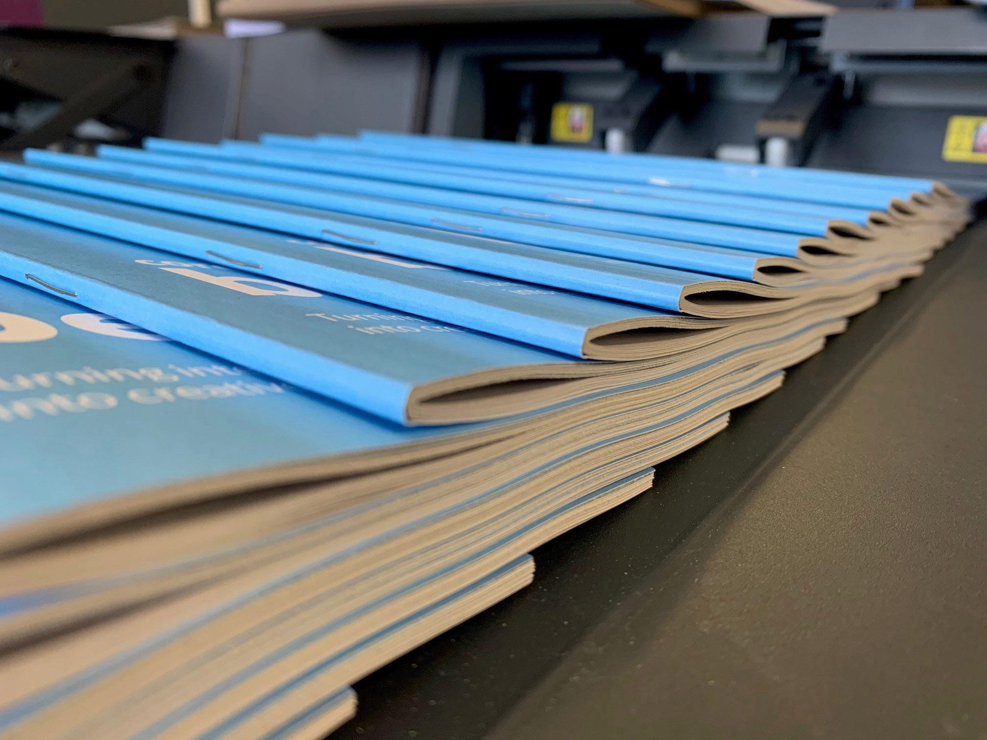 Saddle Stitched Booklets On Printer Conveyor Belt
